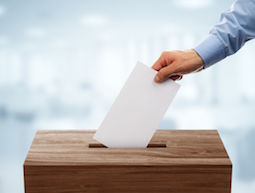 48354981 - ballot box with person casting vote on blank voting slip